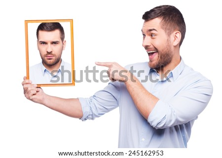 Give me a smile! Handsome young man in shirt holding a picture of himself with upset face and pointing it with smile while standing against white background  - stock photo