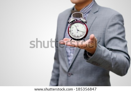 Give more time concept, Alarm clock in businessman hand - stock photo
