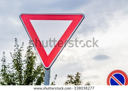 give priority  and no parking signals in the leaves - stock photo