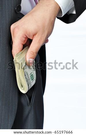 Giving a bribe into a pocket, vertical shot. - stock photo