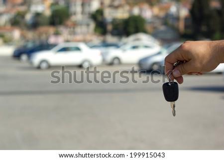 Giving a car key outdoor - stock photo