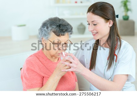 Giving senior lady a glass of water - stock photo