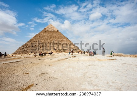 GIZA, EGYPT - NOV 23, 2014: Unidentified tourists and local horse and camel riders in Giza Necropolis, Egypt. UNESCO World Heritage - stock photo