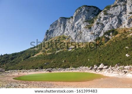 Glacial lake below the high cliffs - stock photo