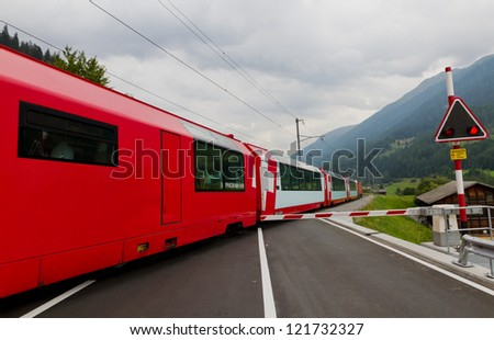 Glacier express train crosses road with closed railway crossing gate, Switzerland - stock photo