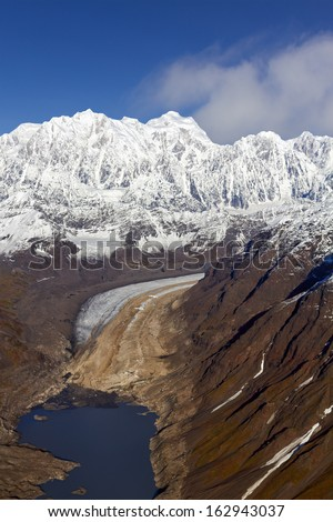 Glacier in the Alaska Mountain Range ending in a lake, Denali National Park and Preserve - stock photo