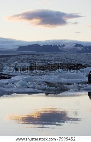 glacier lake on iceland with reflecion of a cloud - stock photo
