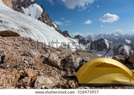 Glacier Tongue and Yellow Tent Mountain View with Ice Glacier and Peaks on Background and Small Single Alpine Yellow Tent located on Rocky Moraine on Foreground - stock photo