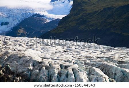 Glacier trekkers walk along a Vatnajokull Iceland - stock photo