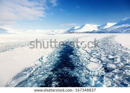Glacier with small iceberg at the Arctic North Pole, Svalbard.In background is Longyearbyen city  - stock photo