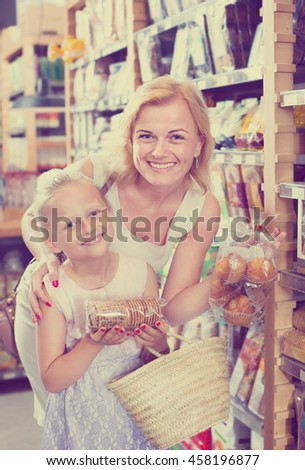 Glad female customer with daughter choosing different cookies and crisp bread in food shop. Focus on both persons - stock photo