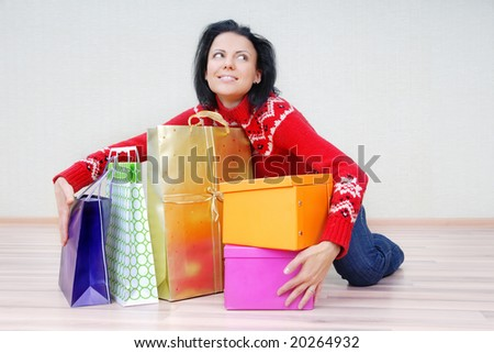 Glad lady indoors with gift shopping presents - stock photo