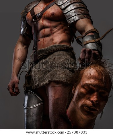 Gladiator covered in blood holding chop off head in his hand - stock photo