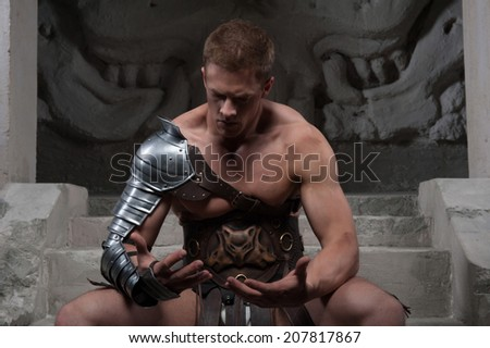 Gladiator in armour sitting on steps of ancient temple and looking at bare hands, on dark background. Concept of masculine power, strength - stock photo
