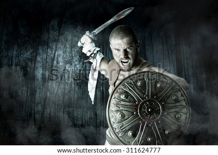 Gladiator or warrior posing with shield and sword battling in a dark forest - stock photo