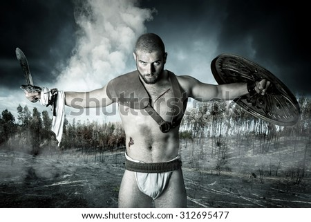 Gladiator or warrior posing with shield and sword outdoors after the battle - stock photo