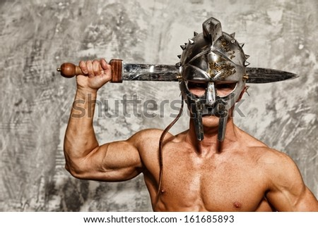 Gladiator with muscular body with sword and helmet - stock photo