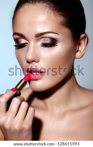 glamor closeup portrait of beautiful sexy Caucasian brunette young woman model applying makeup lipstick on her lips with perfect clean skin - stock photo