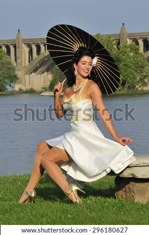 glamor portrait of a beautiful sultry pinup girl with a black parasol - stock photo