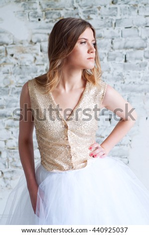 Glamorous beautiful blonde woman in golden sequin outfit and tulle white skirt with glitter makeup - stock photo