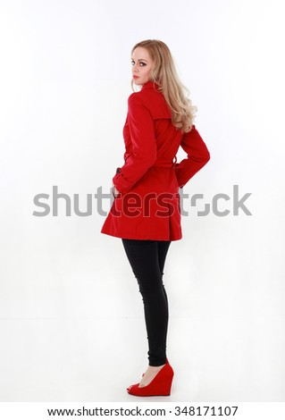 glamorous, beautiful blonde young woman with blonde hair, wearing  long, red winter trench coat. full length standing portrait hands in pocket, walking away from camera. isolated on white background. - stock photo