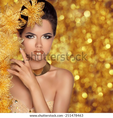 Glamorous beauty fashion girl portrait. Beautiful Young Woman with golden flowers over holiday bokeh lights background. Luxury Hairstyle, makeup, accessories.  - stock photo