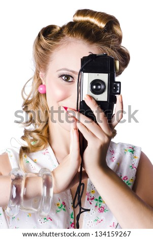 Glamorous blond woman photographer taking a picture with retro film camera on white background - stock photo