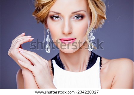 Glamorous blonde girl in a white dress with embellishments on purple background, close up - stock photo