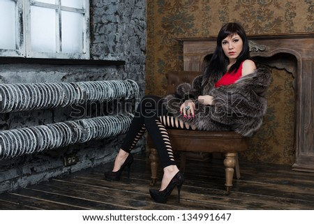 Glamorous caucasian woman in fur coat posing in a vintage interior - stock photo