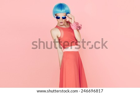 Glamorous fashion Lady in blue wig and sunglasses on pink background. Vanilla style - stock photo