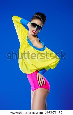 Glamorous fashion model posing in vivid colourful clothes and sunglasses. Bright fashion. Optics, eyewear. Studio shot. - stock photo