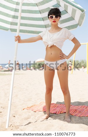 glamorous girl in retro style by color umbrella on the beach. outdoors - stock photo