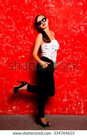 Glamorous girl with red lips and spectacles posing against the red background - stock photo