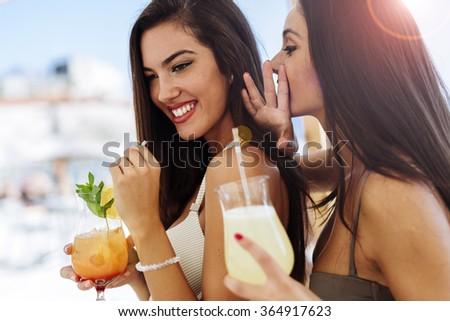 Glamorous girls drinking beverages on sunny beach - stock photo