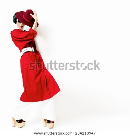 Glamorous lady in trendy vintage red raincoat and hat on a white background - stock photo