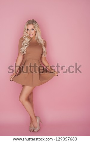 Glamorous leggy blonde woman in a miniskirt posing with her hands holding up the skirt in a flare against a pink studio background with copyspace - stock photo
