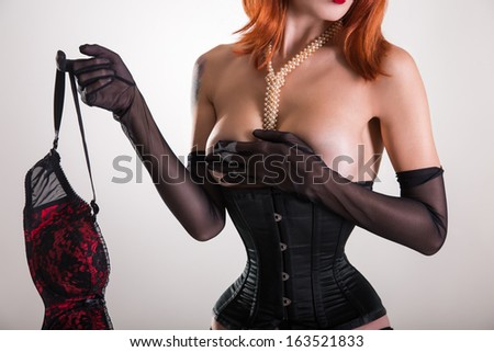 Glamorous pinup woman in corset holding red bra, studio shot on white background  - stock photo