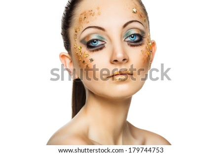 Glamorous portrait of young beautiful girl with big blue eyes, lush lashes and bright golden makeup. Fashion shiny highlighter on skin, velvet skin, gold lips - stock photo