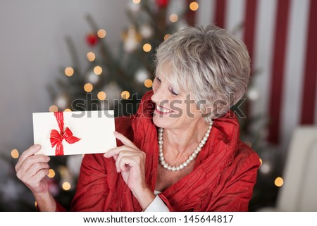 Glamorous retired lady with a christmas gift voucher displaying the blank white envelope with a red ribbon in front of the decorated tree, red and white themed - stock photo