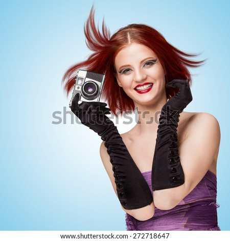 Glamorous smiling girl, wearing long gloves, holding an old vintage photo camera, and saying cheese on blue background. - stock photo