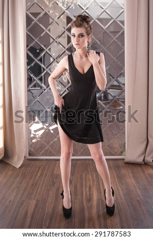 Glamorous woman in black dress posing in the interior - stock photo