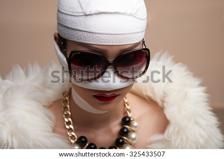 Glamorous woman in face bandage after plastic surgery - stock photo