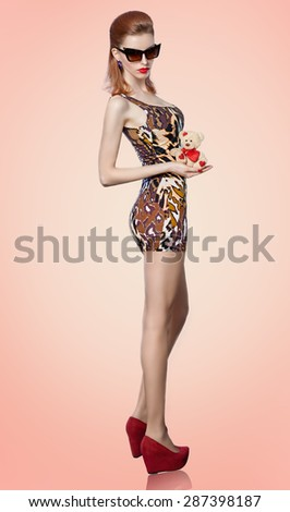 Glamorous  woman in fashionable sunglasses with red lips. Sexy lady  in dress with leopard print holds loving teddy bear with red heart. Beautiful girl  with glowing skin vintage styled. - stock photo