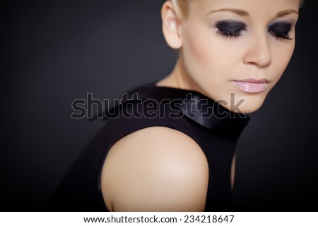 Glamorous woman on a black background with a glossy evening make-up - stock photo