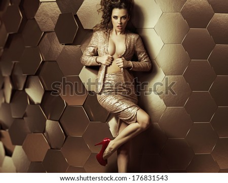 Glamorous woman on wall of gold - stock photo