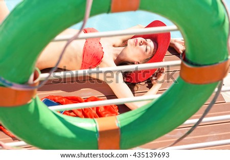 Glamorous woman sun tanning at pool deck of cruise ship - Attractive young female sunbathing on luxury yacht poolside - Summertime holiday concept - Different point of view with focus on subject face - stock photo