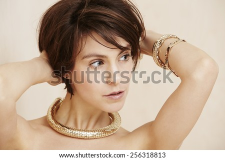 Glamorous woman wearing gold jewelry, looking away - stock photo