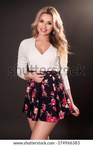 Glamorous young blonde woman in short dress on dark background - stock photo