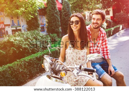 glamorous  young couple sitting on a vintage scooter in the street, man wears a shirt and the woman - a summer dress and sunglasses - stock photo
