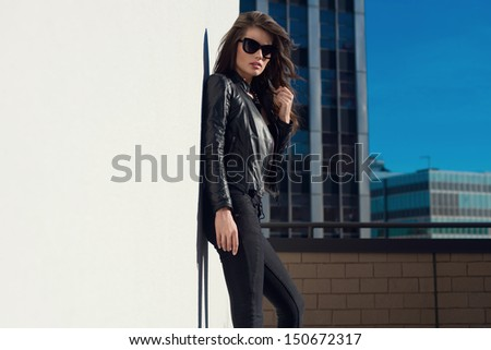 Glamorous young woman in black leather jacket and sunglasses  on the rooftop - stock photo